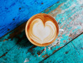 Cafe con leche con corazon sobre mesa azul