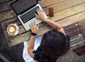 Chica tomando cafe delante de ordenador